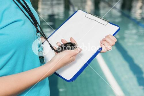 Mid section of coach with a stop watch and clipboard by pool
