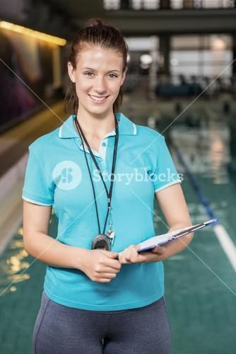 Portrait of female coach with a stop watch and clipboard by pool