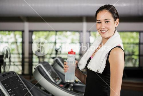 Portrait of happy woman on treadmill holding water bottle