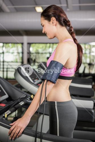 Woman exercising on treadmill with mobile on armband