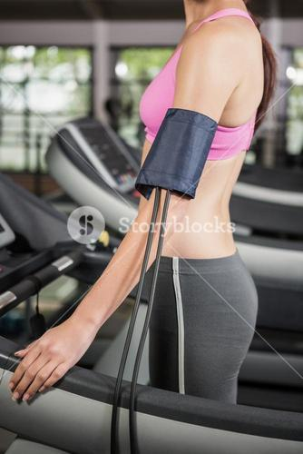 Mid section of woman exercising on treadmill with mobile on armband