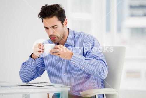 Businessman blowing a hot cup of coffee