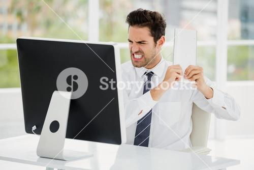 Frustrated businessman holding keyboard in anger