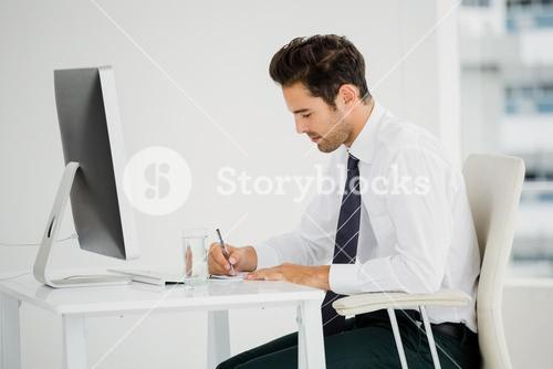 Businessman using computer and taking notes