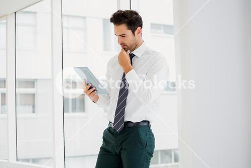 A businessman is holding and reading a notebook
