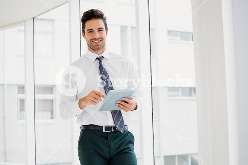A man is holding a notebook and smiling