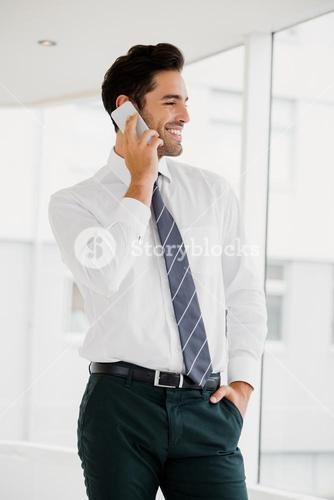 A businessman is calling and looking outside