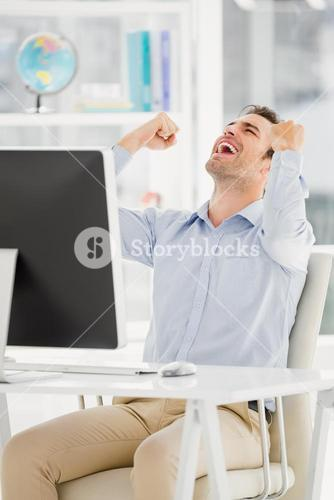 A business is sitting in front of his computer and is happy
