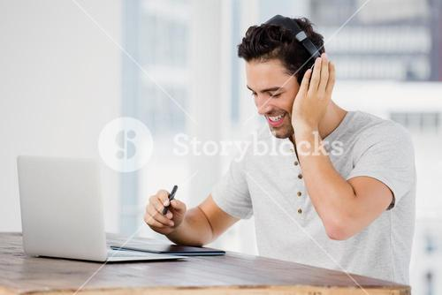 Young man using pen tablet and laptop