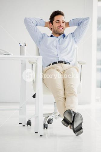 Businessman sitting with hands behind head in the office