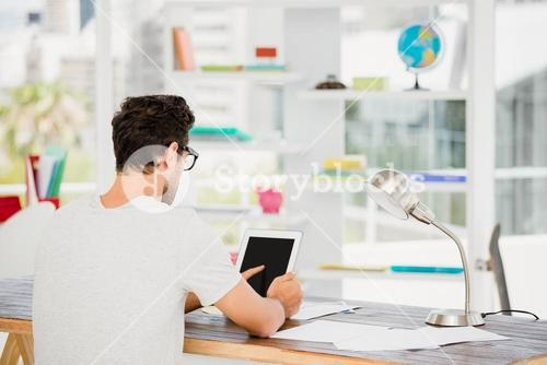 Young man using digital at his desk