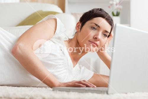 Close up of a serious woman relaxing with a laptop