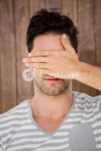 Handsome man covering his eyes