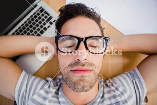 Man in spectacles sleeping on the floor with laptop