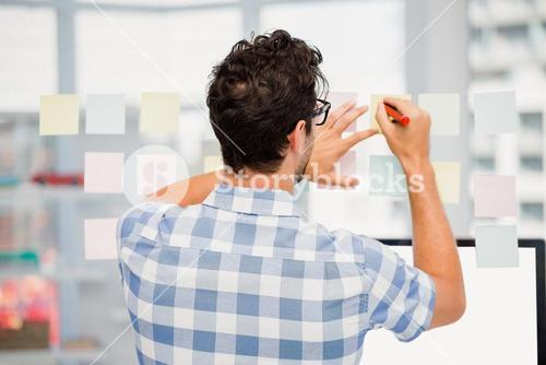Rear view of man writing on sticky notes