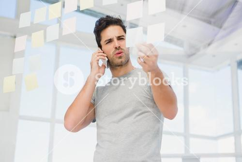 Man looking at a sticky notes while talking on phone