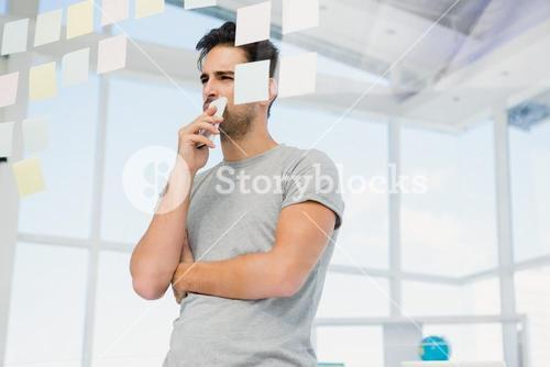 Thoughtful man looking at sticky notes on window