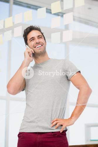 Man talking on phone with hand on hip