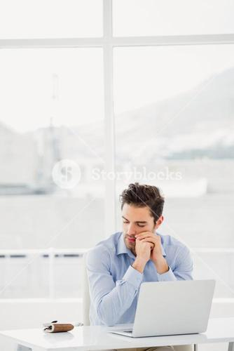 Tensed businessman sitting at table with laptop