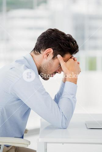 Tensed businessman sitting at table with hand on forehead