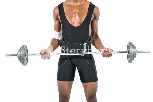 Mid-section of bodybuilder lifting heavy barbell weights