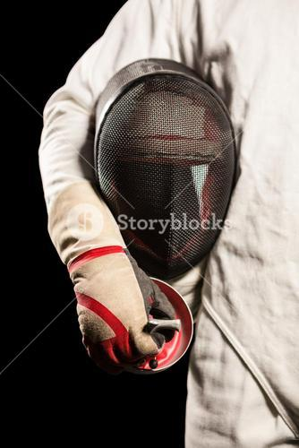 Mid-section of man standing with fencing mask