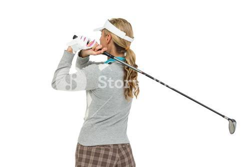 Golf player about to swing a golf ball