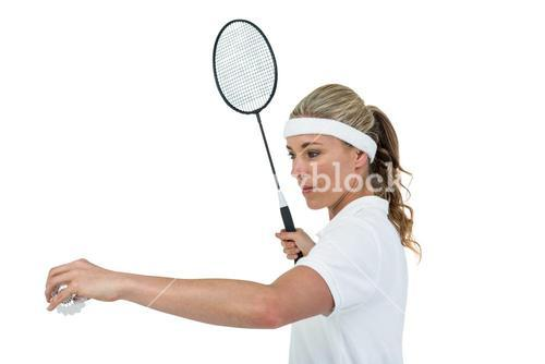 Female athlete holding a badminton racquet ready to serve