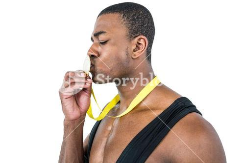 Happy athlete kissing medal