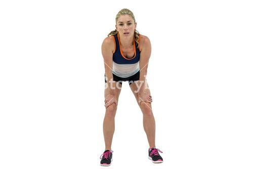 Tired athlete standing with hand on knee
