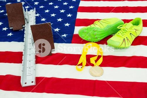 Trainer shoes, starting block and gold medal on american flag