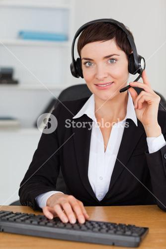 Portrait of a serious secretary calling with a headset