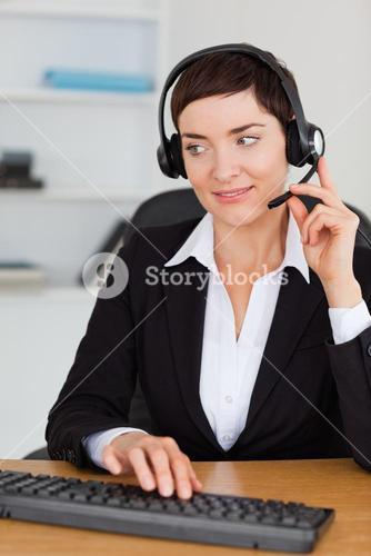Portrait of a professional secretary calling with a headset