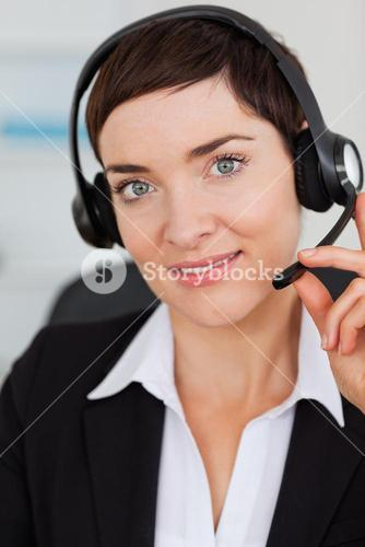 Portrait of a cute secretary calling with a headset