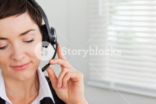Close up of a focused secretary calling with a headset
