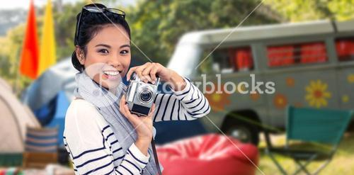 Composite image of smiling asian woman taking photograph with camera