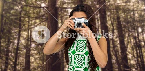 Composite image of asian woman taking picture with digital camera