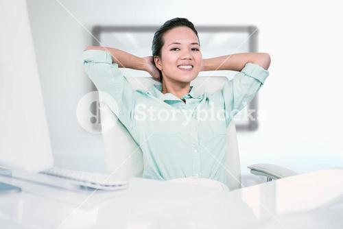 Composite image of smiling businesswoman with hands behind head
