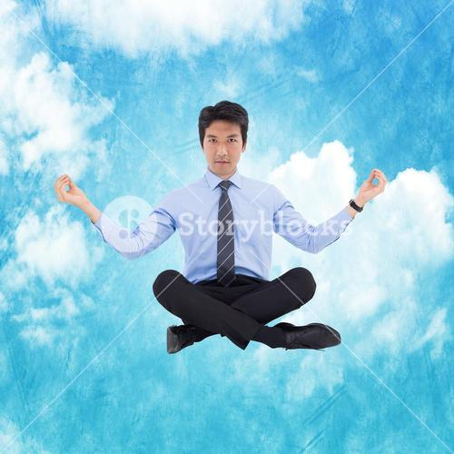 Composite image of asian businessman doing yoga