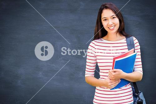 Composite image of college girl holding books with blurred students in park