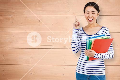 Composite image of cheerful woman pointing up while holding files