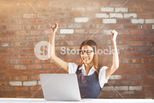 Composite image of happy businesswoman using laptop and raising arms