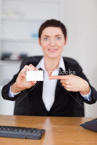 Portrait of a secrertary pointing at a blank business card