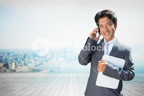 Composite image of confident estate agent standing at front door on the phone