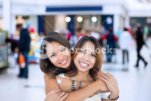 Composite image of two pretty sisters posing in front of the camera