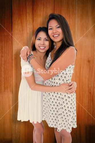 Composite image of two sweet sisters hugging each other