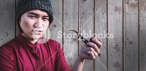 Composite image of thoughtful hipster smoking pipe