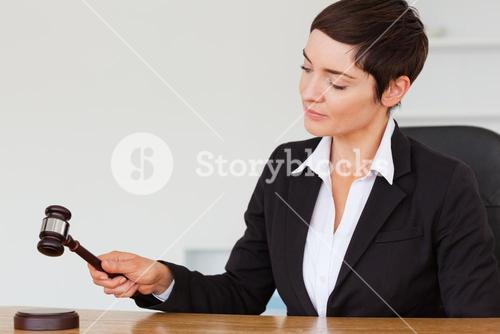 Serious woman knocking a gavel