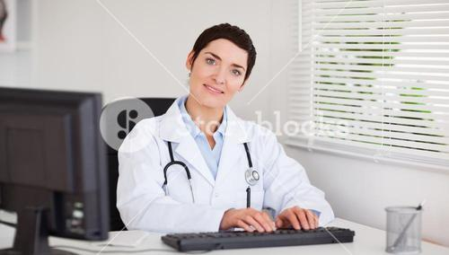 Smiling doctor typing with her computer