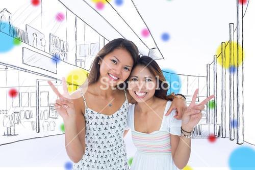 Composite image of two smiling young women making a peace gesture